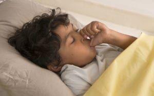 Child sleeping while sucking thumb